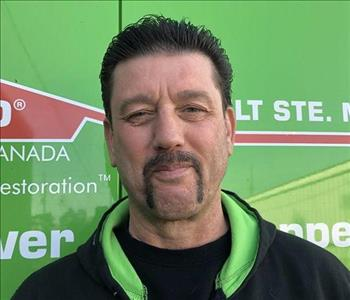Male with brown eyes and short black hair and a black handle bar mustache wearing a SERVPRO hoodie.